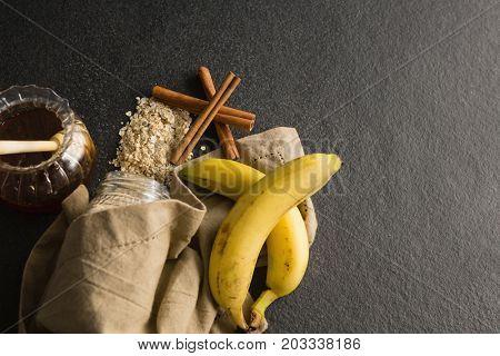 Close-up of honey, banana, oatmeal, cinnamon sticks on black background