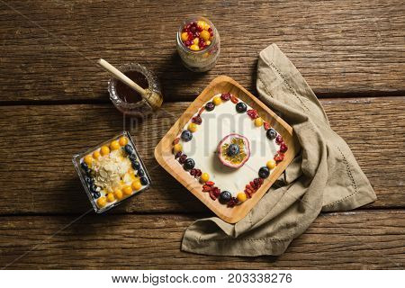 Overhead view of various fruit cereals and honey on a wooden table