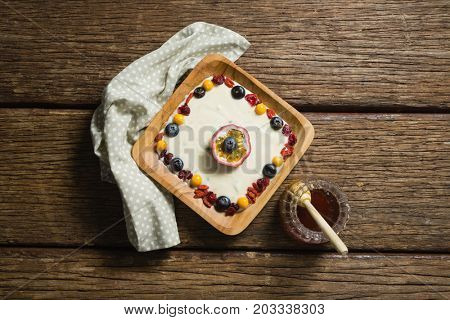 Overhead view of fruit yogurt and honey on a wooden table