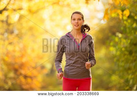 Young brunette woman running in autumn forest listening to mps music. Lifestyle and sport photo of healthy style. Outdoor and nature fitness exercise.