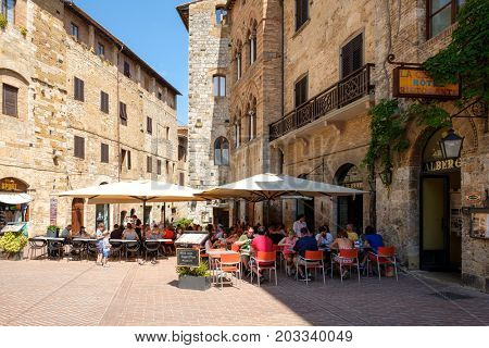 SAN GIMIGNANO,ITALY - JULY 23,2017 : Tourists at a restaurant on the medieval town of San Gimignano in Tuscany