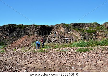 TERSKY COAST, RUSSIA - JULY 29, 2017: Visiting tourists looking for fragments of an amethyst bristle among the waste rock piles of the old Cape Ship amethyst field on the White Sea coast