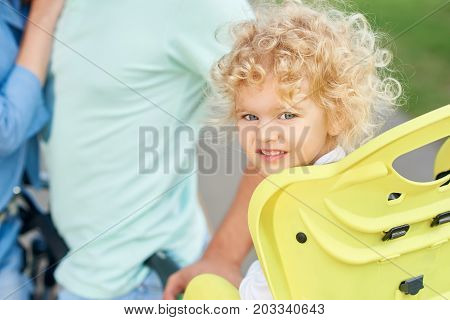 Shot of a cute little blonde haired baby girl sitting in a baby bike seat her parent hugging on the background copyspace marriage family love affection children kids parenting active lifestyle concept