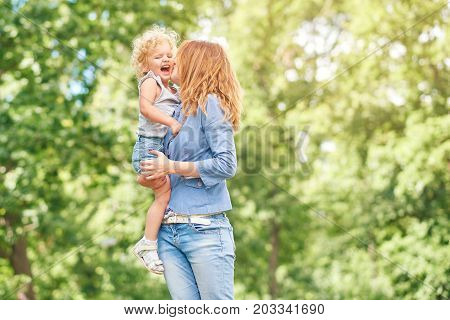 Shot of a loving mother holding her cute baby girl kissing her on a cheek while outdoors at the park copyspace motherhood parent happiness love family children kids concept.