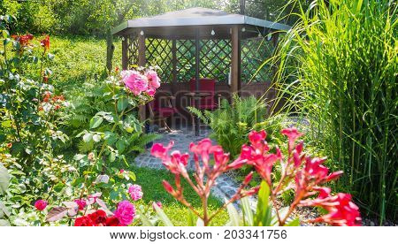 a Garden Pavilion behind flowers in the sunshine