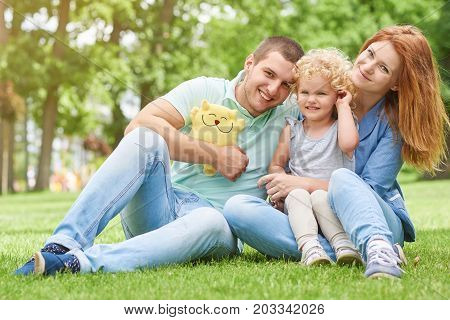 Shot of a happy young family sitting on the grass at the park together smiling to the camera copyspace lifestyle leisure weekend holidays love parenting parents children kids emotions.