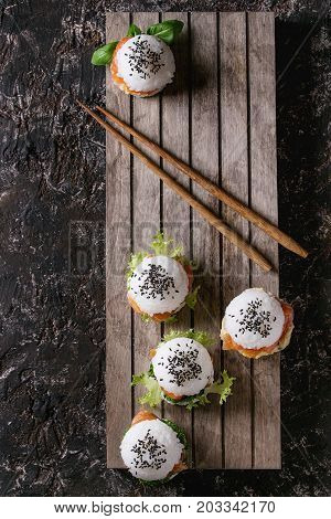 Mini rice sushi burgers with smoked salmon, green salad and sauces, black sesame served on wood pallet tray with chopsticks over dark brown concrete background. Modern healthy food. Top view