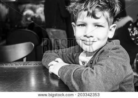 beautiful portrait of a smiling boy with banged hair, black and white photography