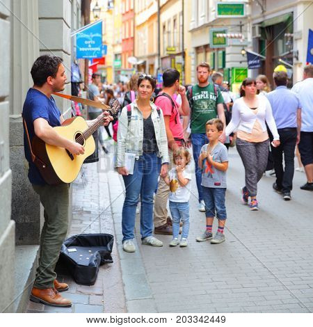 Stockholm, Sweden - July 25, 2017: Unidentified musician plays guiar for tourists in central shopping street of Gamla Stan in Stockholm