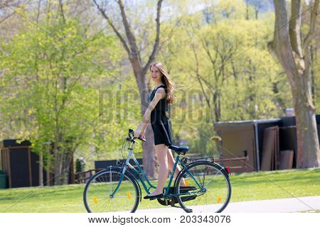 Portrait view of girl on bicycle wearing on black short dress. Young happy Woman riding along road on green spring  outdoor Park. Sporty young girl riding a bicycle on a sunny morning