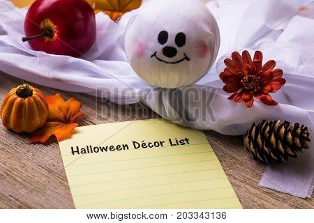 Halloween Decor list concept on notebook and wooden board