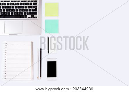 Business working at an office Modern white office desk table with laptop computer smartphone and notebook. Top view with copy space flat lay.