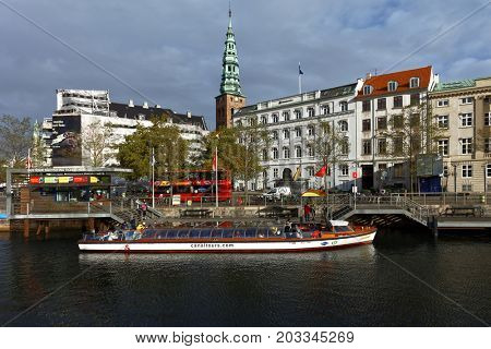 COPENHAGEN, DENMARK - NOVEMBER 7, 2016: Sightseeing bus and tour boat at Ved Stranden street. Sightseeing tours is very popular among tourists