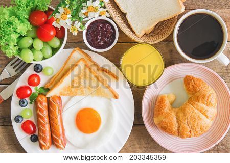 Homemade breakfast with sunny side up fried egg toast sausage fruits vegetable croissant strawberry jam black coffee and orange juice in top view flat lay concept.Delicious homemade american breakfast. American breakfast concept background.