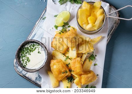 Traditional british fast food fish and chips. Served with white cheese sauce, lime, parsley, french fries in frying basket on white paper over blue concrete background. Top view.