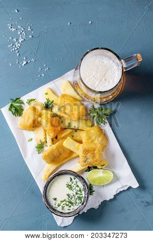 Traditional british fast food fish and chips. Served with white cheese sauce, lime, parsley, glass of lager beer on white paper over blue concrete background. Top view.