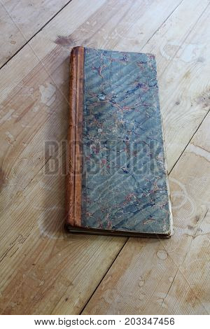 Antique ledger with marbleized paper cover, diagonal on table, vertical view