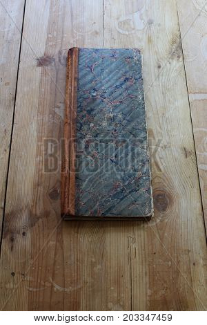 Vintage ledger with marbleized paper cover, straight on the table, vertical view
