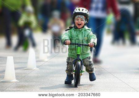 Little boy riding a runbike on a rainy day