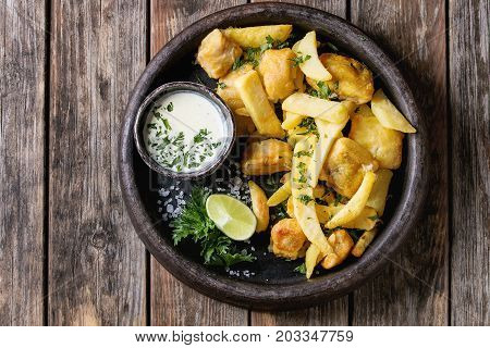 Traditional british fast food fish and chips. Served with white cheese sauce, lime, parsley, french fries in frying basket in terracotta tray over old wooden plank background. Top view with space