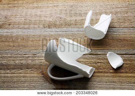 Broken Coffee Cup on a Wooden Background