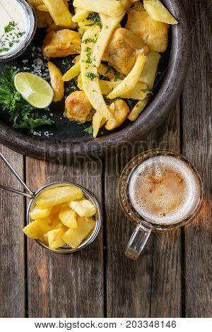 Traditional british fast food fish and chips. Served with white cheese sauce, lime, parsley in terracotta tray, glass of lager beer over old wooden plank background. Top view with space