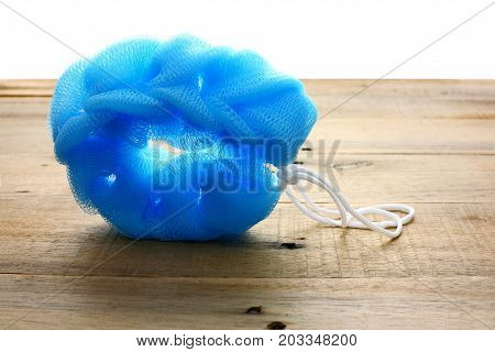 Blue Body Scrubber on a Wooden Background