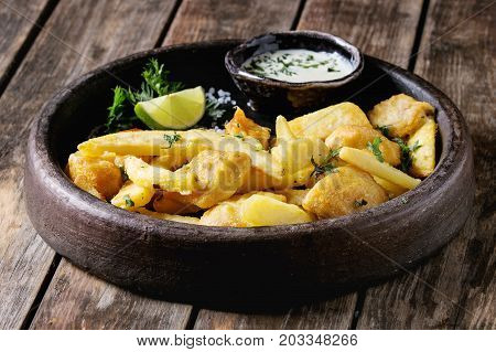 Traditional british fast food fish and chips. Served with white cheese sauce, lime, parsley in terracotta tray over old wooden plank background. Close up