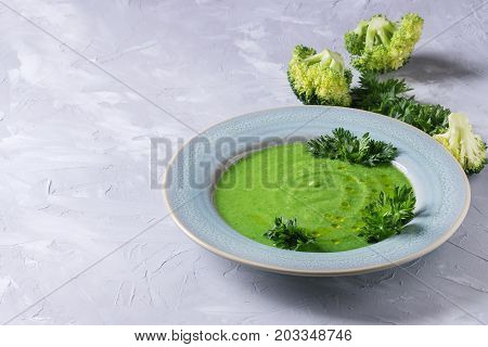 Vegetarian vegan broccoli cream soup served in blue plate with fresh parsley and broccoli over gray concrete background. Copy space. Healthy eating.