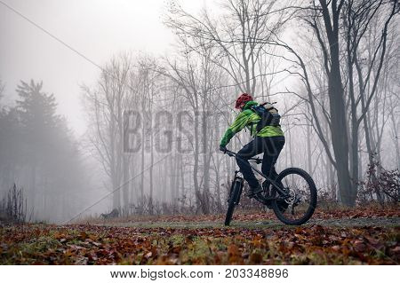 Mountain biker riding on trail in woods. Mountains in winter or autumn landscape forest. Man cycling MTB on rural country road. Sport fitness motivation and inspiration.