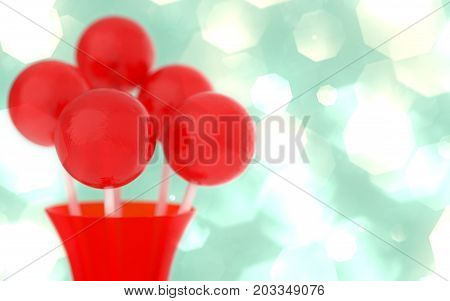 Red balls of lollipops on a stick in a red vase on a retro background with glowing bokeh effect. Macro shot with shallow DOF. Horizontal wide pop art style poster with round candies