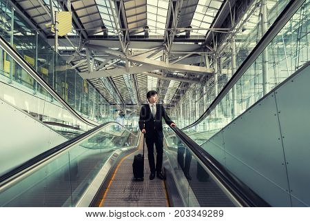 Asian young businessman with luggage down the escalator in airport. Business travel concept.