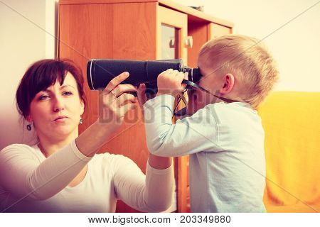 Child passion and hobbies concept. Kid playing with big professional digital camera photographing various things in house mother looking after him.
