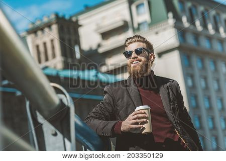 handsome man with disposable cup of coffee outdoors