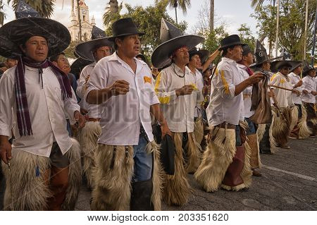 June 29 2017 Cotacachi Ecuador: men wearing extra large hats and chaps during Inti Raymi celebration