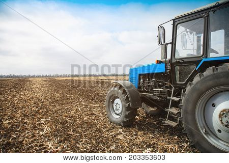 Old blue tractor in a empty field on a bright sunny day. Agricultural machinery field work.