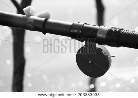 Black-and-white photo with old fishing rod in retro style close-up against the backdrop of lake and bokeh