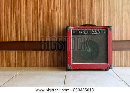 The old guitar amplifier with wooden walls background.