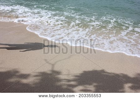 Shadows of men and tree on the beach gulf of Thailand.