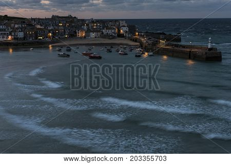 Saint Ives England - April 29 2017: Night in the harbor city and church with beach of Saint Ives in Cornwall England.
