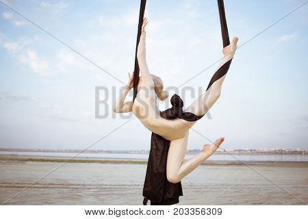 exercises with aerial silk outdoor, sky background. beautiful fit woman training acrobatic in airt.