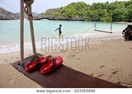 Red Slipper on the wooden cradle on the beach with people activety background on the island in Thailand.