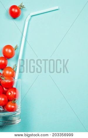 Tomato juice or smoothie, recipe ingredient healthy eating, healthy drink concept, organic detox vegetable, cherry tomato in drink glass with straw. Flat lay with copy space, multi color background.