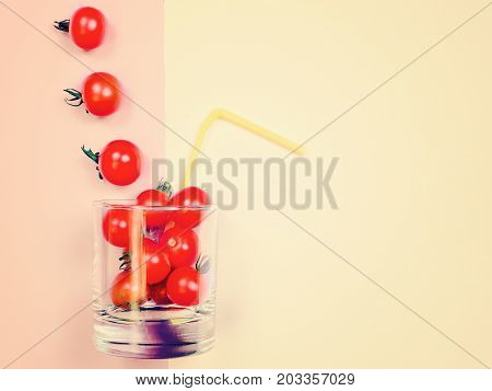 Tomato juice or smoothie, recipe ingredient healthy eating, healthy drink concept, organic detox vegetable, cherry tomato in drink glass with straw. Flat lay with copy space, multi color background. Retro vintage toned