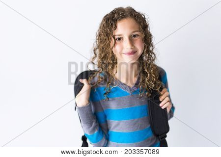 the girl of 9 years in a school uniform poses in studio.