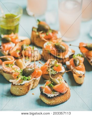 Crostini with smoked salmon, pesto sauce, watercress and capers and pink grapefruit cocktails over light blue background, selective focus. Party, catering or fingerfood concept