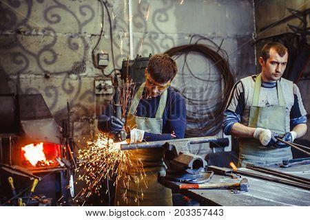 Craftsman sawing metal sparkles all around workshop. Working at noon.