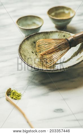 Japanese tools for brewing matcha tea. Matcha powder in tin can, Chasen bamboo whisk, Chawan bowl, cups for ceremony, grey marble background, selective focus, copy space