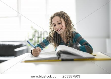 the girl of 9 years in a school uniform doing homework