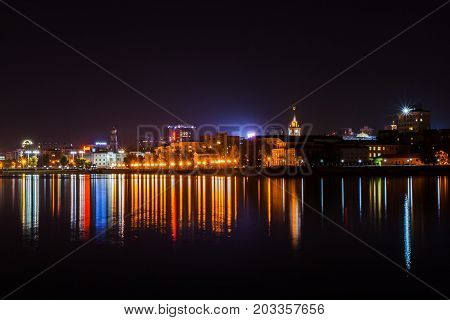 Yekaterinburg Russia - September262016: The evening water area of the city pond. Evening city lights and their reflection in water of pond. Ekaterinburg is the largest city of the Ural with population of about 1.5 million.